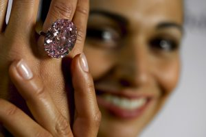 "A model shows during a press preview on September 25, 2013 a 59.6-carat pink diamond that will be auctioned by Sotheby's in the Swiss city of Geneva in November at a record asking price of $60 million (49 million euros). ""The Pink Star"", an internally flawless oval-cut vivid pink diamond, will become the most valuable diamond ever to be offered at auction, Sotheby's said. AFP PHOTO / FABRICE COFFRINI (Photo credit should read FABRICE COFFRINI/AFP/Getty Images)"