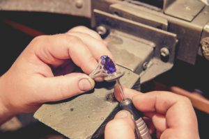 Master jeweler produces a gold ring with a big blue stone
